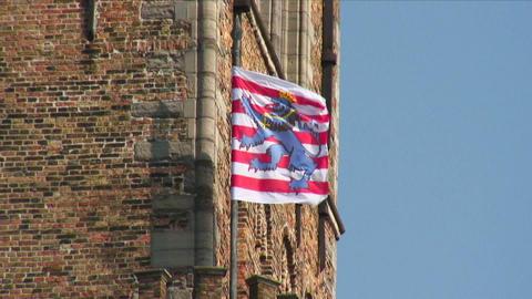 Bruges, Belgium heraldic flag flying on a pole at a building corner Live Action