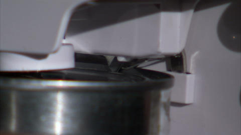 Extreme close up on black of electric can opener opening a can Live Action