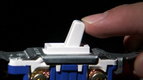 Close up of a light switch being flipped Live Action