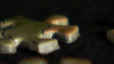 Close up pan of puzzle pieces on a black surface Live Action