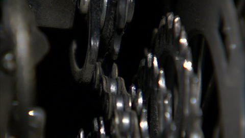 Close up of a bike chain shifting over rotating gears Live Action