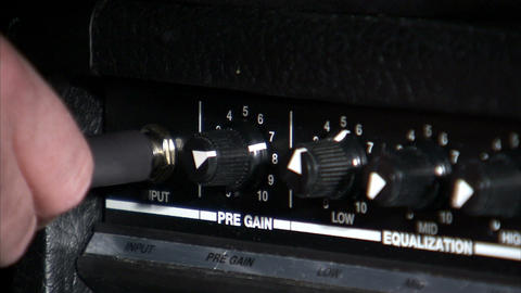 Guitar cord being plugged into a guitar amp Footage