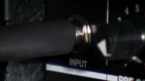 Close up of guitar cord plugging into an amp Footage