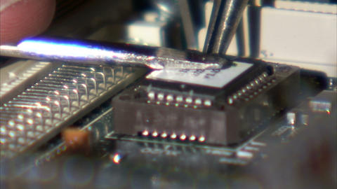 Close up of a computer chip being placed onto a circuit board Footage