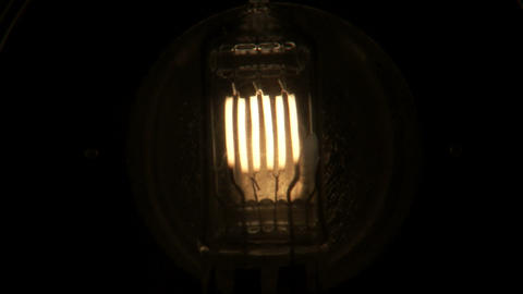 Close up of a light bulb with several filaments flickering on then off Footage