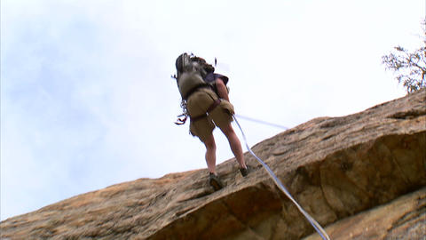 Rock climber rappelling down a cliff Footage