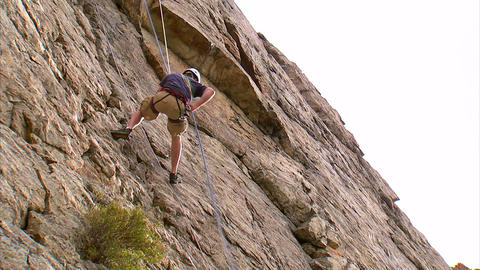 Rock climber jumping across a cliff face Footage