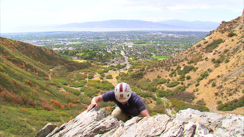 Shot of a rock climber coming over the top edge of a cliff Footage