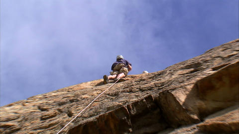 Rock climber climbing up a cliff Footage