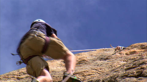 Shot of a rock climber climbing up a cliff Footage