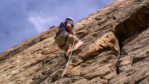 Shot of a mountain climber climbing up a cliff Footage