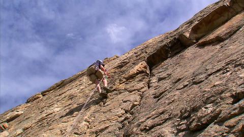 Clip of a mountain climber climbing up a cliff face Footage