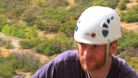 Clip of a rock climber coming over the top edge of a cliff Footage