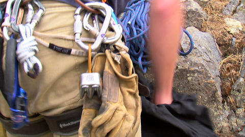 Mountain climber packing his pack with gear Live Action