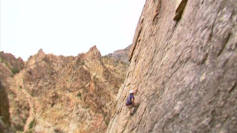 Mountain climber hopping across a cliff face Footage