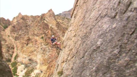 Shot of a mountain climber hopping across a cliff face Footage