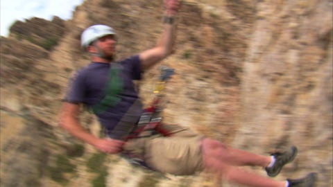 Rock climber hopping over the camera Footage