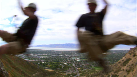 Two rock climbers swinging over the camera Live Action