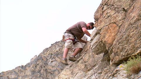 Clip of a mountain climber climbing down a cliff Footage