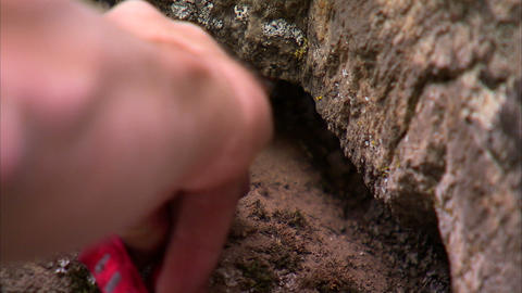 Climber's hand placing a cam in a rock crack Footage