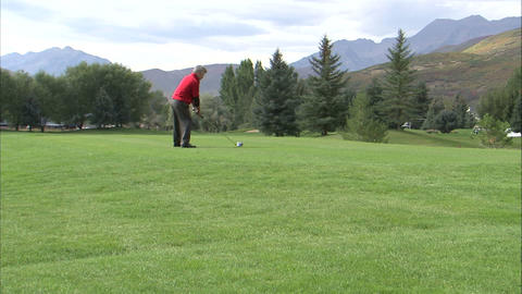 Shot from behind a golfer teeing off Footage