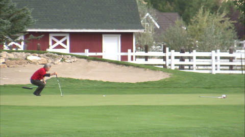 Golfer taking some practice putts on the green Footage