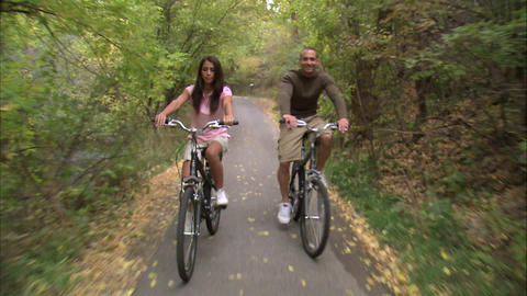 Couple riding their bikes through a tree-covered path Footage