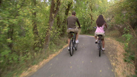 Couple riding their bikes down a tree-covered path Live Action