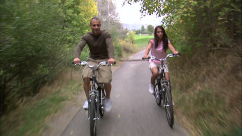 Man and woman riding their bikes down a path Footage