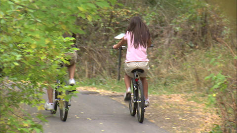 Man and woman on bikes on a tree-covered path Footage