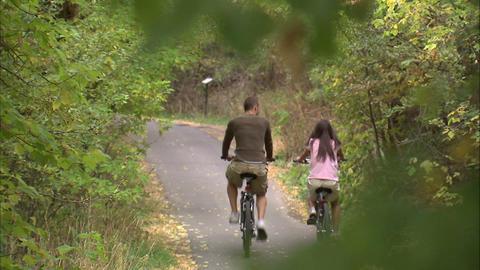 Man and woman riding their bikes through trees Footage