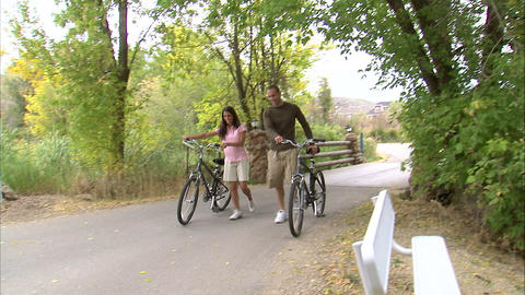 Couple walking their bikes down a path Live Action