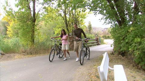 Couple walking their bikes down a path Footage