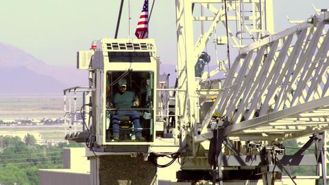 A construction worker operates a crane high above Salt Lake City Footage