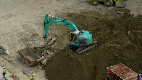 A backhoe lifts large rocks from atop a dirt pile Footage