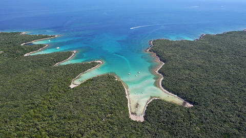 Aerial - Amazing white sand beaches with clear blue water. Boat driving into bay Footage
