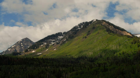 Time-lapse of a mountaintop with snow patches amid greenery Footage