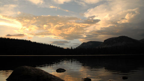 Silhouetted time-lapse of a mountain lake at sunset Footage