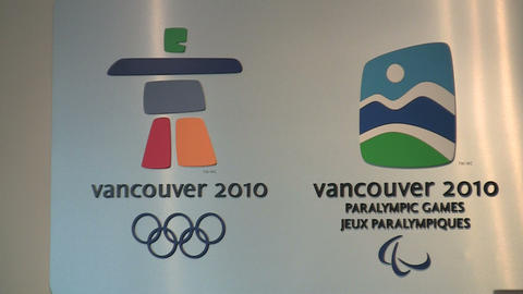 People looking at a bilingual Vancouver Olympics sign Footage
