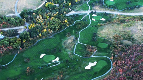 Aerial shot of golf course with water and colored tree Footage