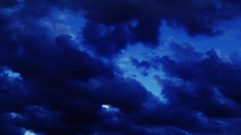 Dark clouds in a deep blue sky roll left across the sky Footage