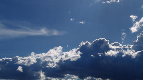 Dark, illuminated clouds roll across a blue sky Footage