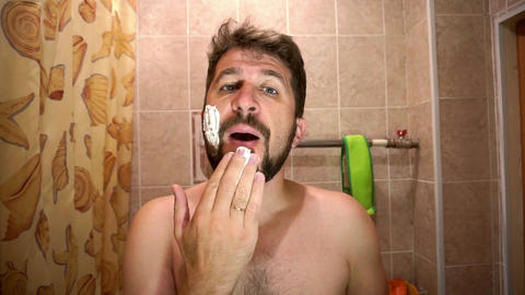 Middle aged man with a full beard applies shaving cream to his face Footage