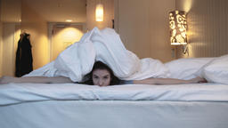 Young Woman Playing Peekaboo From Under Bed Sheets Footage