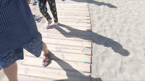 Wooden walkway on the beach with people legs passing by GIF