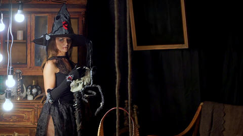 The Halloween witch standing with a staff and petting a human skull Footage