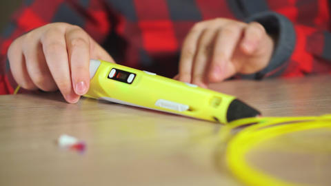 Teen boy inserts a piece of yellow ABS plastic in a 3D pen. He creates a plastic Footage