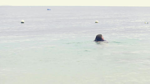Young woman swimming in sea water while summer vacation. Tourist woman swimming ビデオ