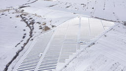 Aerial drone view of snow covered solar panel park, photovoltaic power station GIF