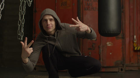 Gangster rapper in hoodie making cool hand gesture Footage